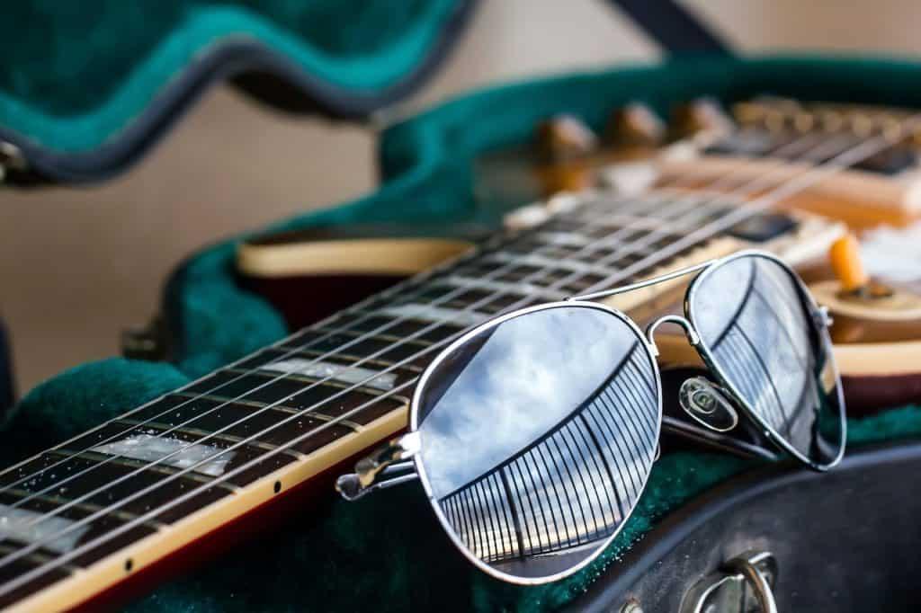 Imagem mostra o braço de uma guitarra e um óculos de sol aviador ao lado.