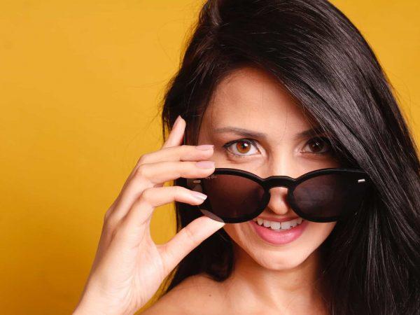 Foto de uma mulher morena abaixando um óculos no rosto, sorrindo, em um fundo amarelo.