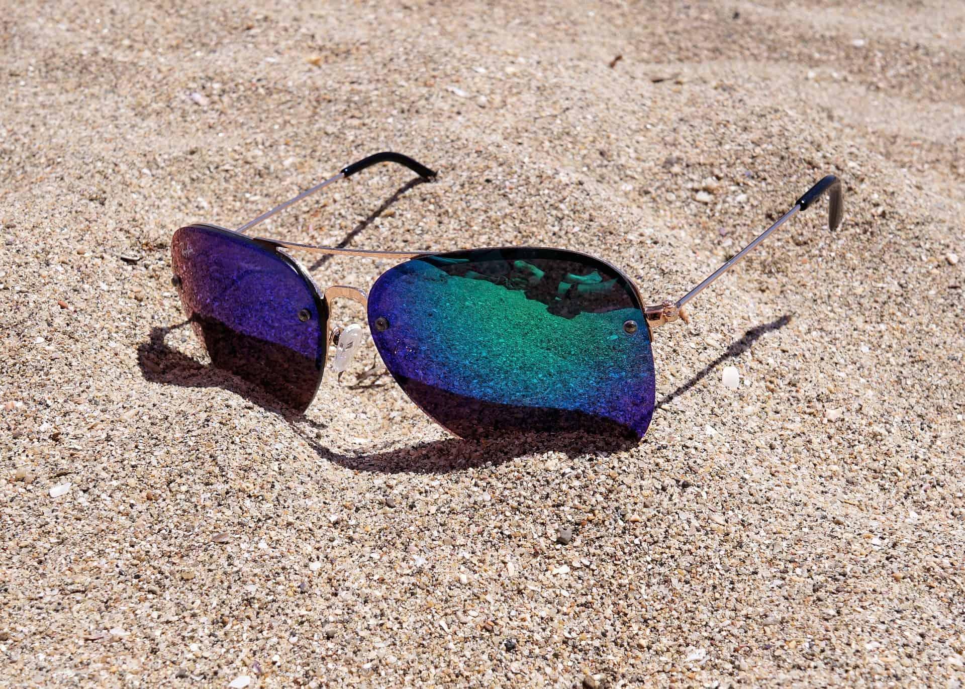 Imagem mostra um óculos de sol na areia refletindo a praia.