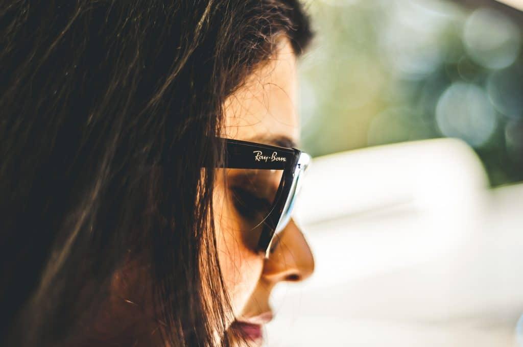 Mulher com óculos de sol Ray Ban.