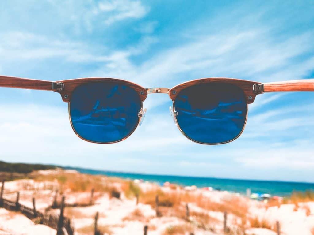 Foto da parte interior de um óculos modelo Club Master Ray Ban, com armação de madeira. Ao fundo, em blur, o céu azul e uma praia.