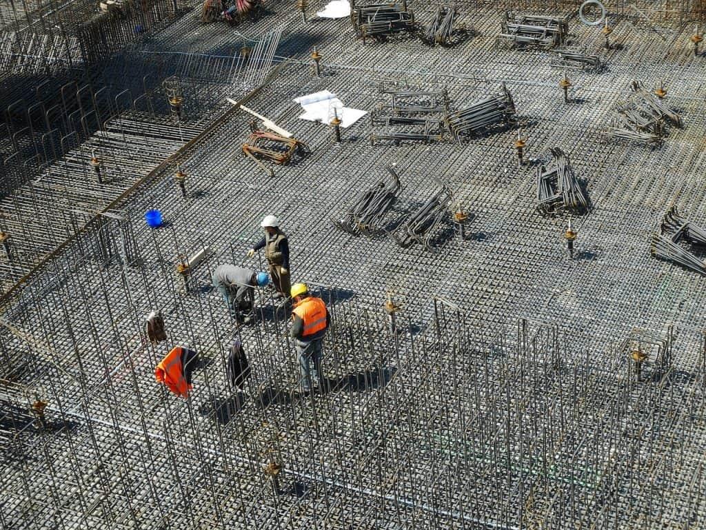 Fotografia aérea de um grupo de trabalhadores sobre uma laje, instalando ferragens.