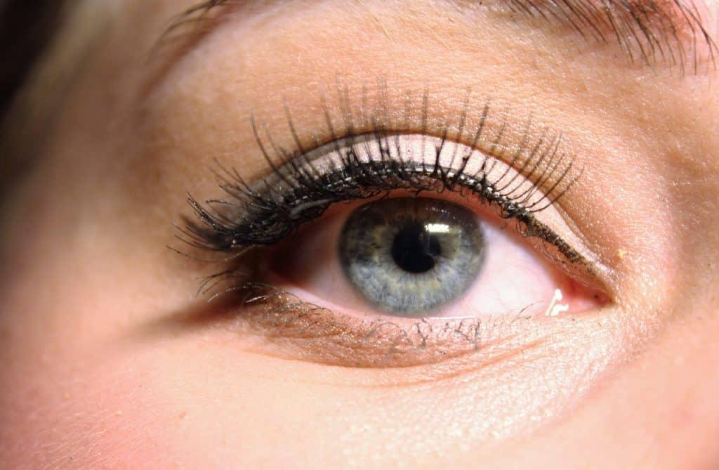 Foto que mostra um olho azul com sombra e delineador além dos cílios postiços colado.