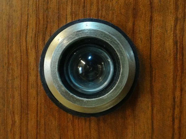 Foto mostra um olho mágico tradicional em uma porta de madeira.