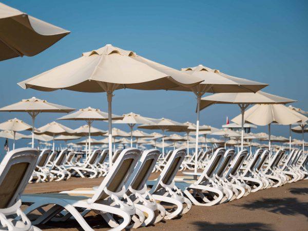 Imagem de ombrelones oferecendo sombra para espreguiçadeiras em praia.