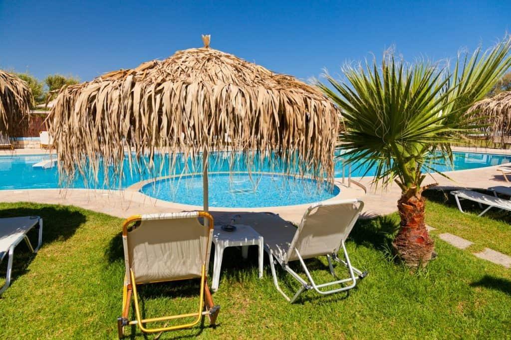 Imagem de ombrelone com cobertura em palha, posicionado diante de piscinas, oferecendo sombra para espreguiçadeiras.