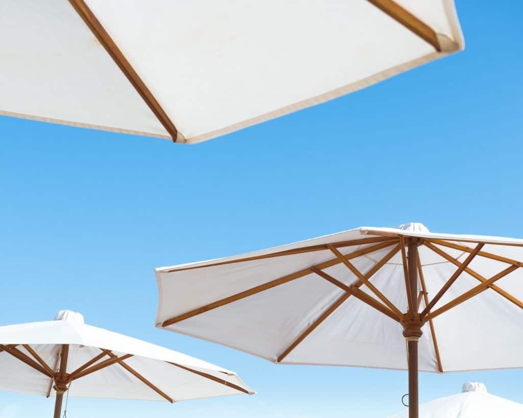 Imagem de alguns ombrelones de madeiras com céu azul no fundo.