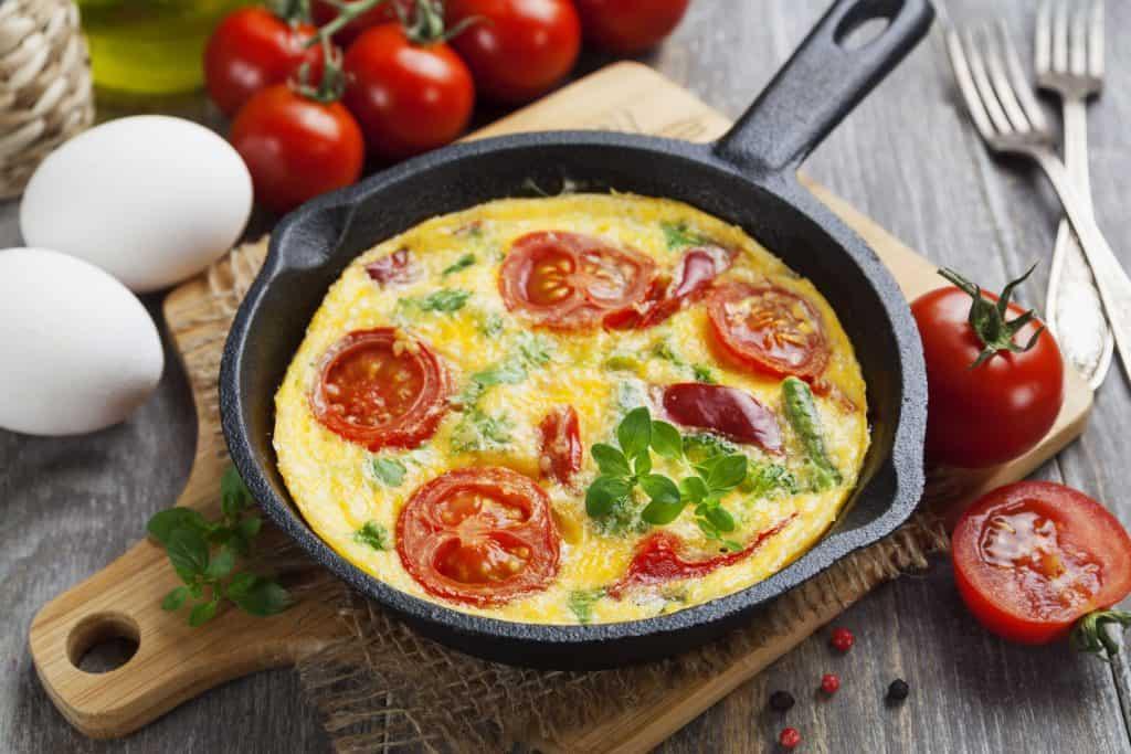 Imagem mostra uma frigideira de ferro com omelete dentro sobre uma tábua de madeira e alimentos ao redor.