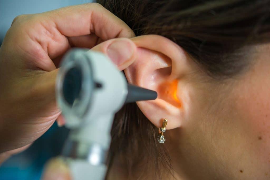 Na foto está um médico examinando a orelha de uma senhora.