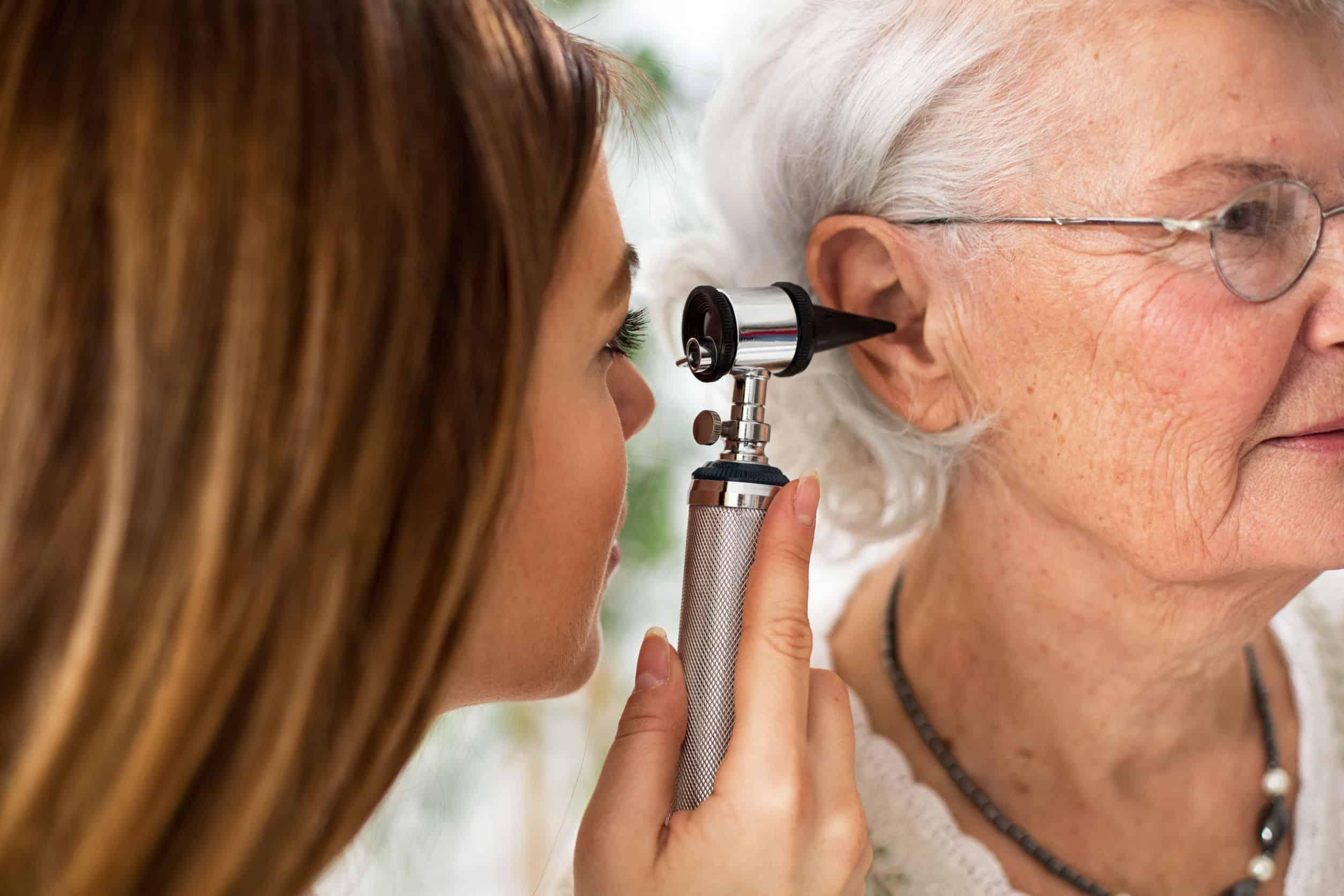 Na foto é possível ver uma médica examinando uma senhora com um otoscópio.