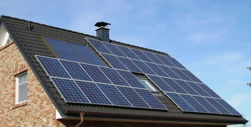 Telhado de uma casa de tijolinhos a vista com grande painel solar.