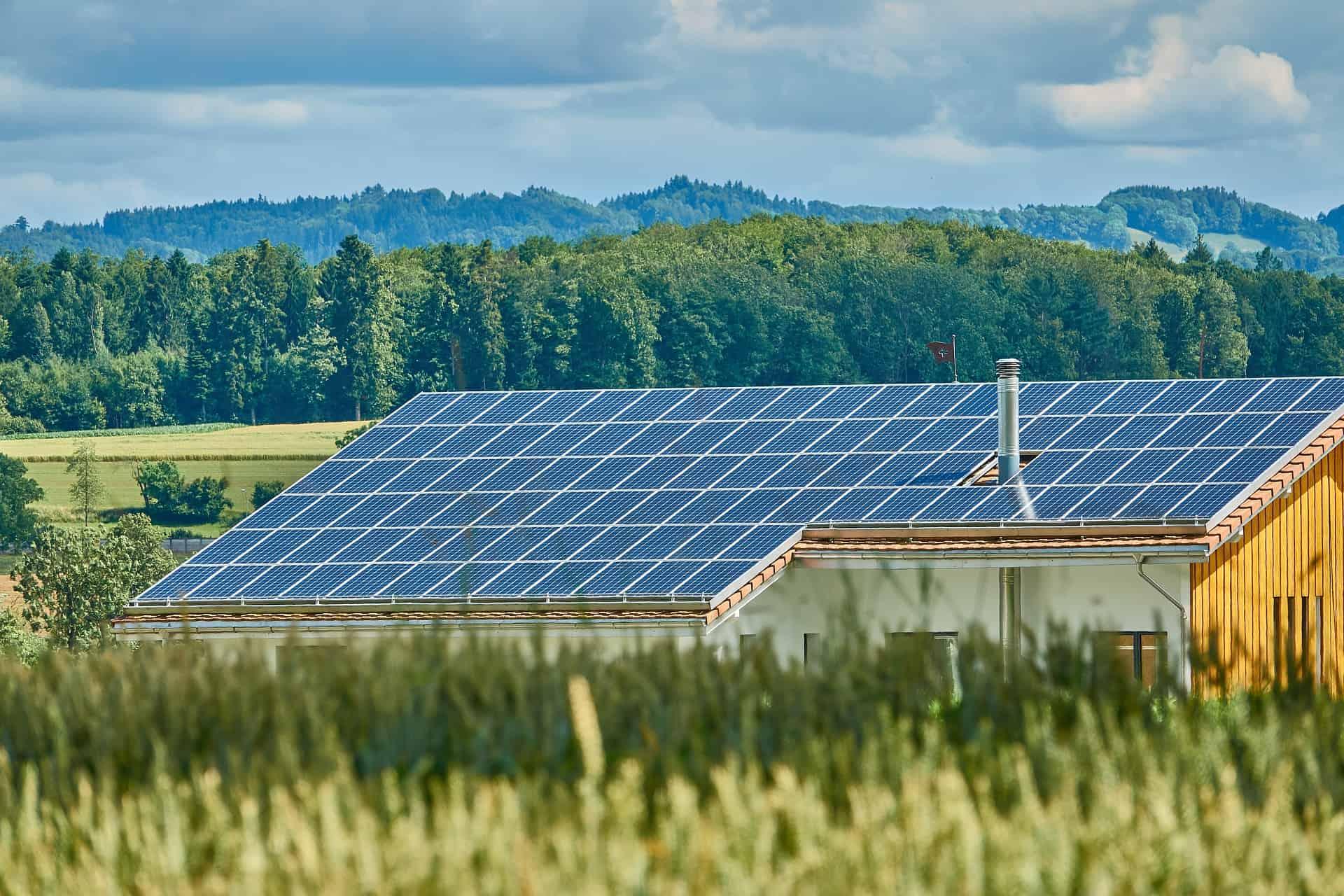 Foto de uma construção em meio à vegetação, com o telhado coberto de painéis solares, deixando espaço apenas para uma saída de chaminé.