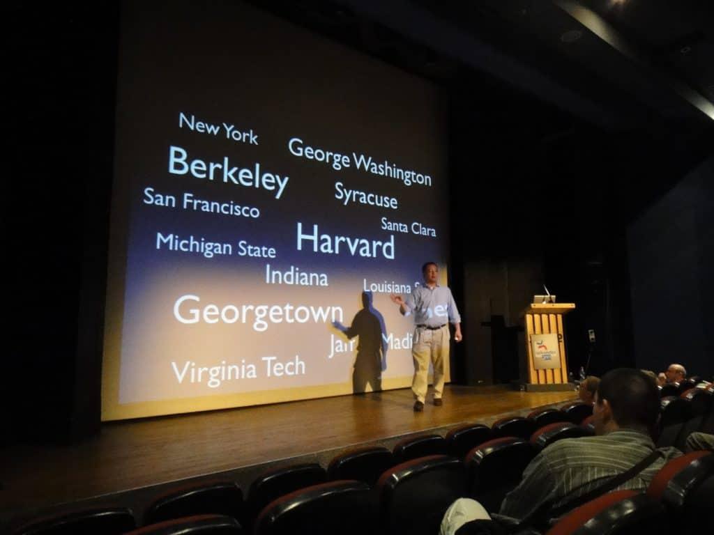 Imagem mostra um homem fazendo uma palestra em um auditório.