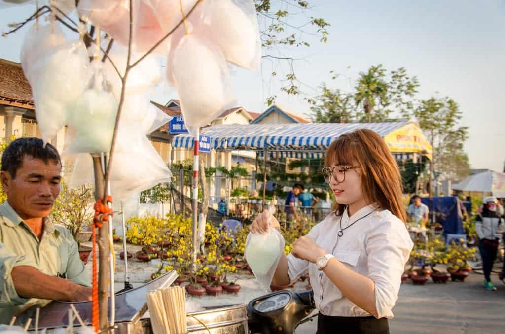 Mulher comprando algodão doce em uma feirinha de rua.