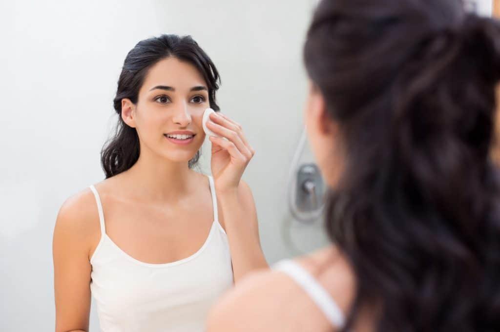 Mulher limpando a pele do rosto.