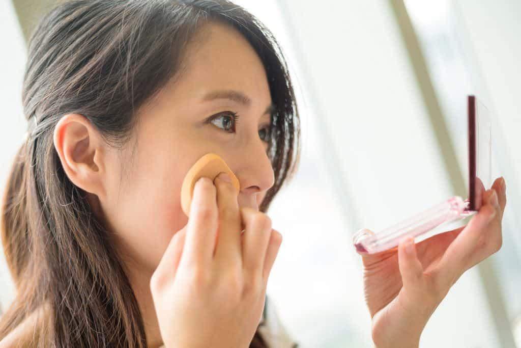 Foto tirada de lado, de uma mulher oriental aplicando com uma esponjinha, algum produto na pele enquanto olha para um pequeno estojo de maquiagem com espelho.