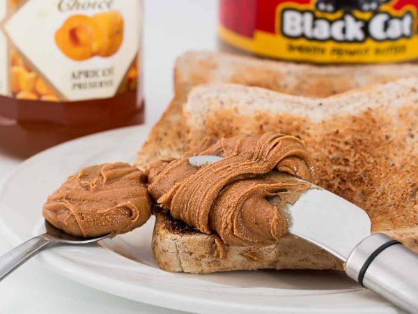 Imagem de pasta de amendoim em colher e espátula por cima de uma fatia de pão.