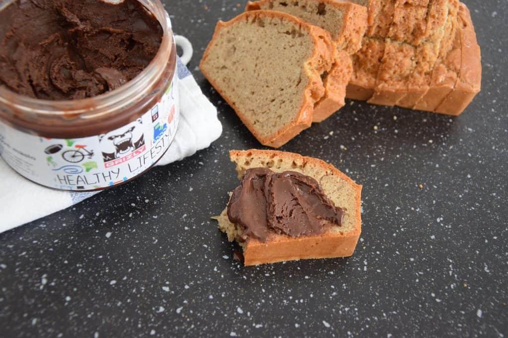 Imagem de pasta de amendoim com sabor de chocolate sobre pão cortado.