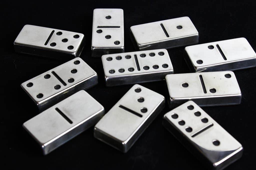 Imagem mostra dez peças de dominó feitas de metal, com suas faces numéricas voltadas para cima, repousando sob uma superfície escura.