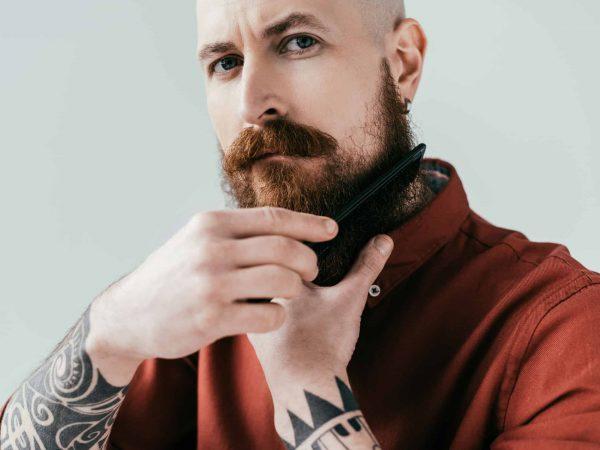 Imagem de homem passando pente na barba.