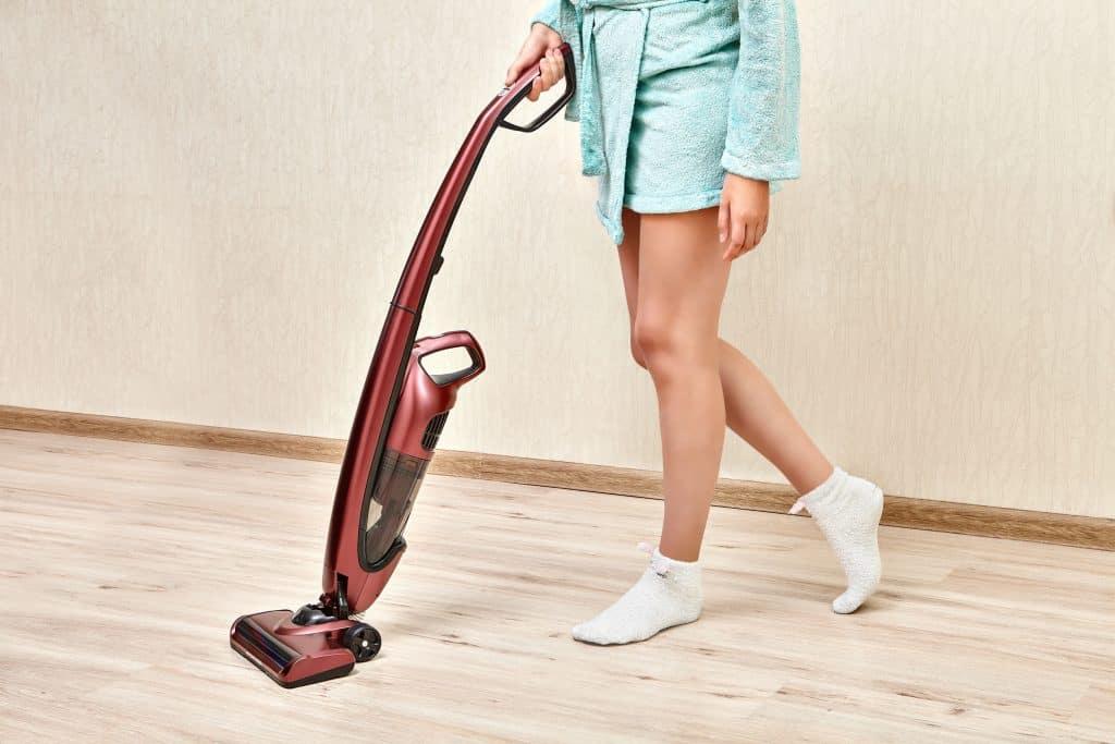Mulher usando aspirador vertical no chão.