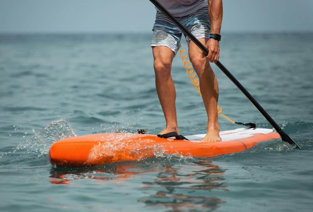 Imagem mostra um close de uma pessoa remando seu stand up inflável no mar.