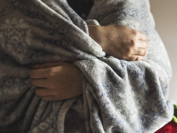 Imagem de pessoa enrolada em cobertor de microfibra cinza