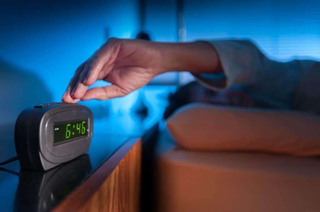 Uma pessoa deitada na cama, com braço esquerdo esticado para apertar o botão de um despertador digital em cima do criado-mudo.
