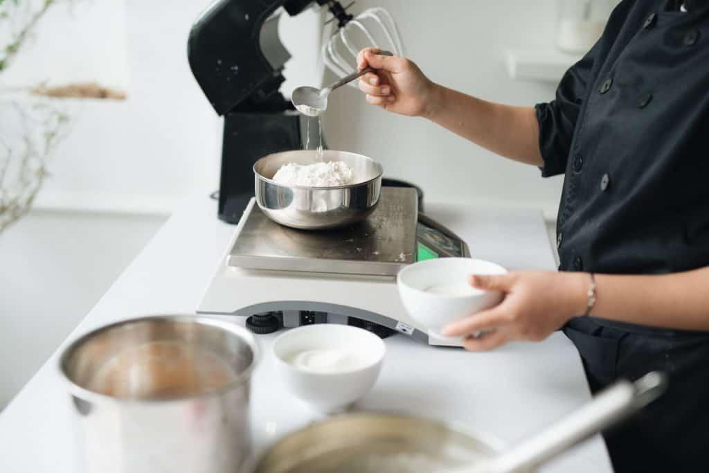 Na foto uma mulher dentro de uma cozinha colocando farinha em um recipiente em cima de uma balança.