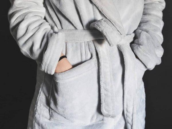 Foto que mostra parte de um roupão cinza, no corpo de uma pessoa, que está com as mãos nos bolsos.