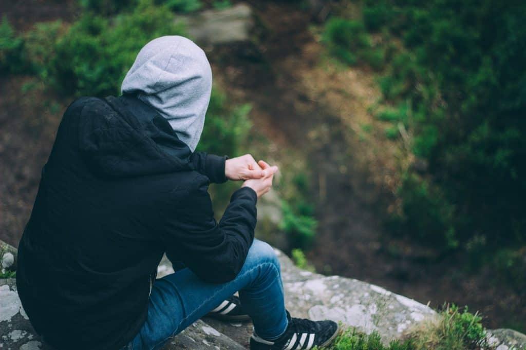 Na foto um homem de costas sentado em uma pedra olhando para um paisagem.