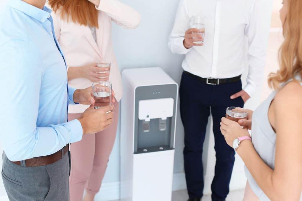 Pessoas bebendo água em volta de bebedouro.