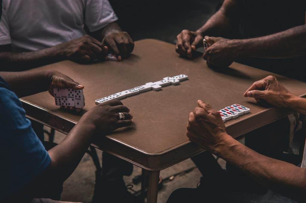 Imagem mostra um jogo de dominó numa mesa de metal, mas apenas os braços dos jogadores são mostrados.
