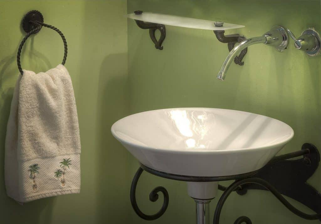 Uma pia redonda em um sifão metálico no banheiro.