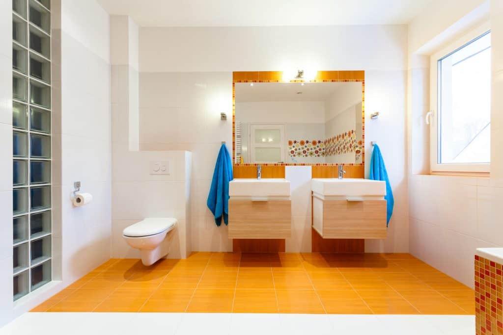 Na foto um banheiro com duas pias, um espelho grande, dois armários, uma privada no canto esquerdo e duas toalhas azuis.