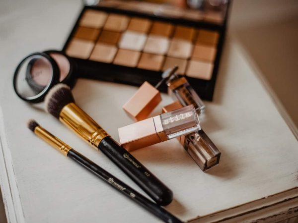 Foto de uma superfície branca com diversas maquiagens, como: pincéis, batom, rímel, paleta de sombras e blush.