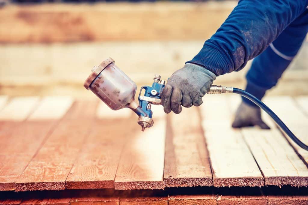 Imagem mostra a mão de um homem usando uma pistola de pintura para pintar madeira.