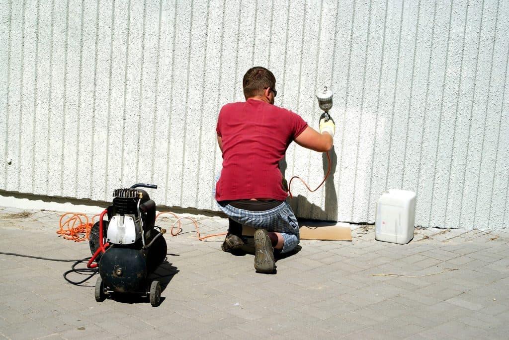 Imagem mostra um homem usando uma pistola de pintura para pintar um muro branco.