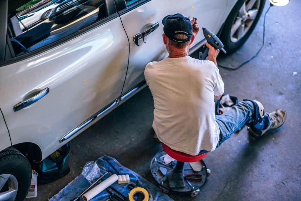Imagem mostra um homem sentado efetuando reparos em um automóvel.