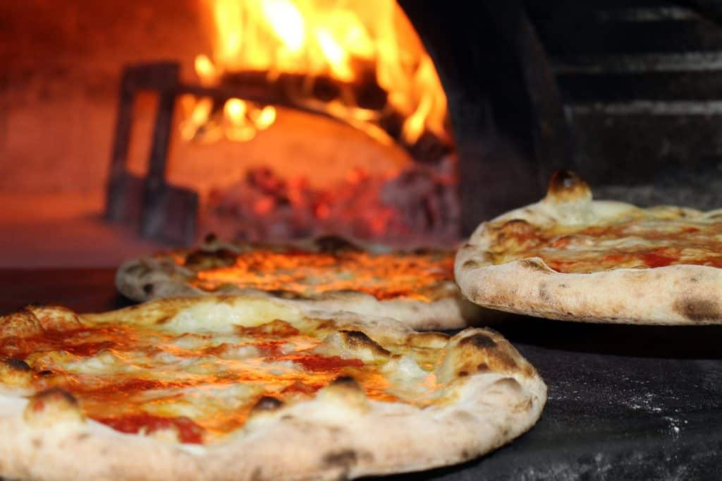 Imagem de pizzas dentro de forno a lenha.