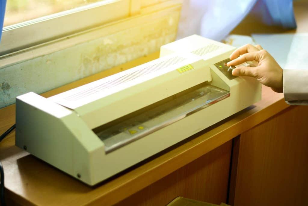Imagem mostra uma mão mexendo em plastificadora.