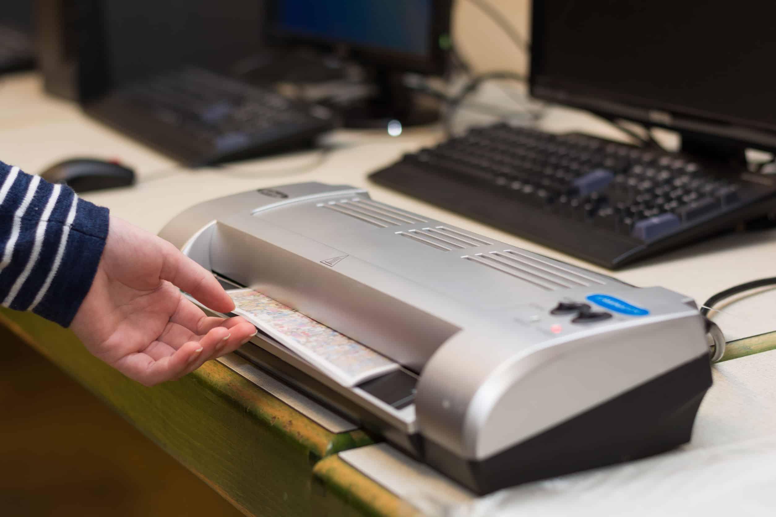 Imagem mostra uma mão inserindo um papel em uma laminadora.