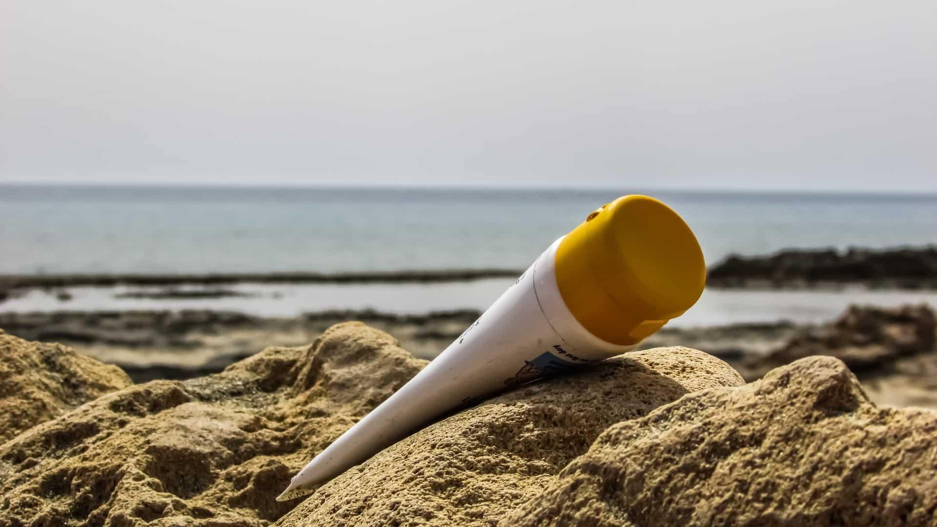 Imagem de pote de pós-sol apoiado na areia da praia.