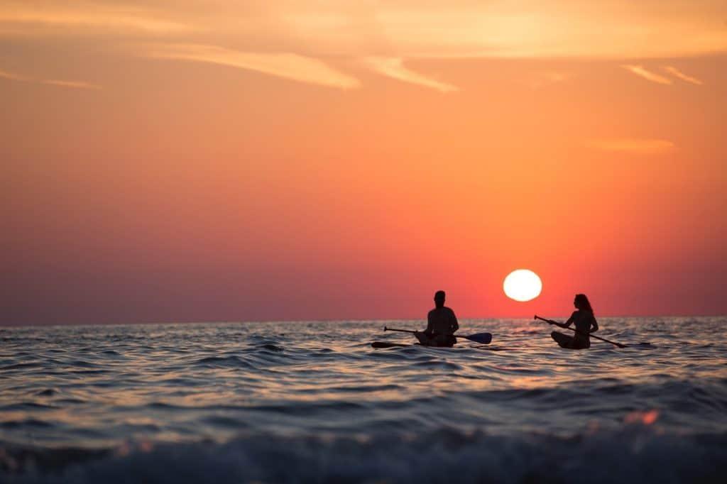 Imagem mostra um casal relaxando sob um par de pranchas de stand up, sob o lusco-fusco do pôr do sol.