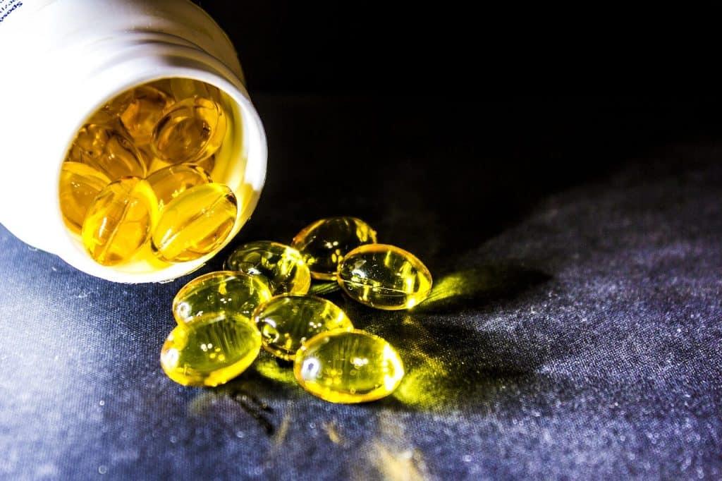 Imagem mostra um frasco de cápsulas de óleo derramando seu conteúdo sobre uma superfície escura.
