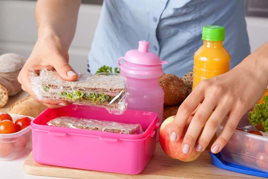 Mulher colocando alimentos em tupperware.
