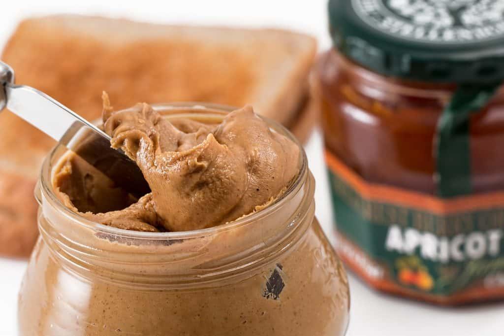 Imagem de pote de pasta de amendoim aberta com pote de geleia e pão ao fundo.
