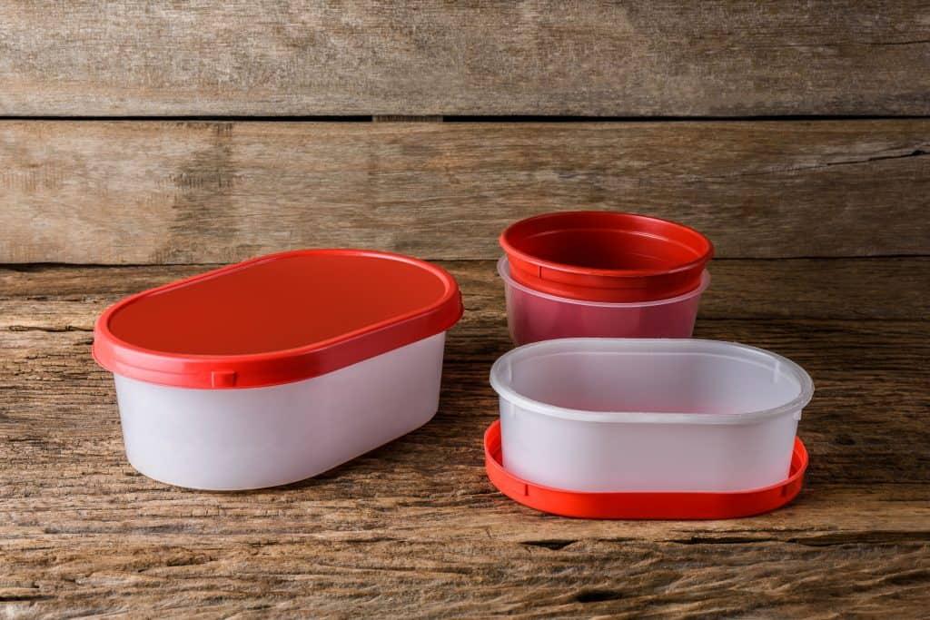 Três potes de plástico transparentes com detalhes em vermelho.