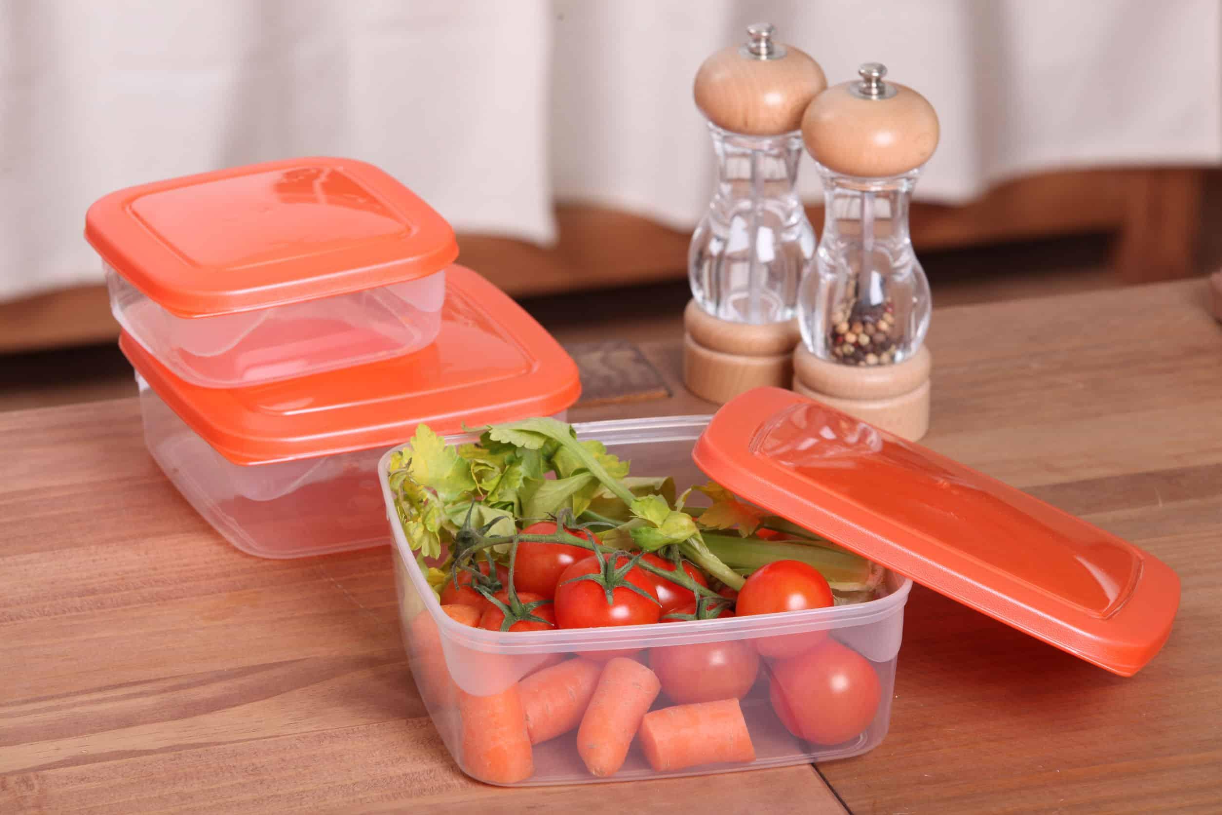 Potes de plásticos fechados e abertos, com alimentos dentro, saleiro e pimenteiro atrás.