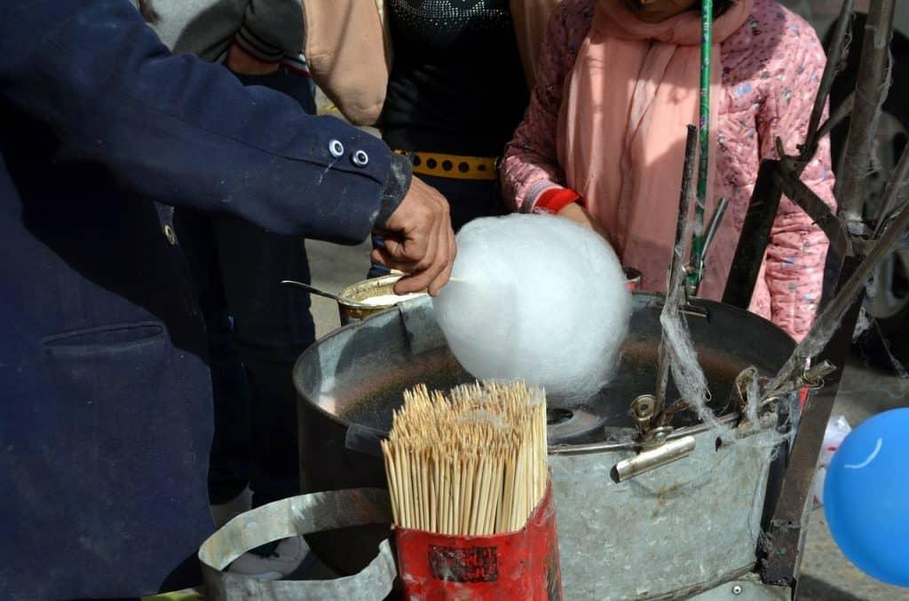 Imagem focada em mão de homem fazendo algodão doce branco na máquina.